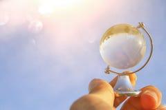 мужская рука держа малый кристаллический глобус перед голубым небом Стоковое Фото