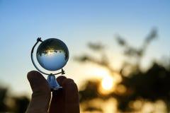 мужская рука держа малый кристаллический глобус перед заходом солнца Стоковые Фото