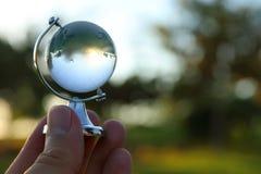 мужская рука держа малый кристаллический глобус перед заходом солнца Стоковые Изображения