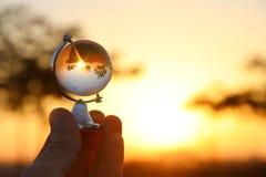 мужская рука держа малый кристаллический глобус перед заходом солнца Стоковое Фото