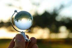 мужская рука держа малый кристаллический глобус перед заходом солнца Стоковое Изображение
