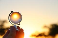 мужская рука держа малый кристаллический глобус перед заходящим солнцем Стоковые Фотографии RF