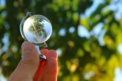 мужская рука держа малый кристаллический глобус Стоковые Изображения