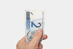 Мужская рука держа национальную валюту Бразилии Стоковое фото RF