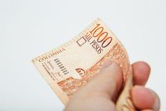 Мужская рука держа национальную валюту Колумбии Стоковые Фотографии RF