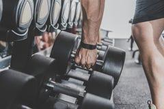 Мужская рука держа оборудование спорта в спортзале Стоковая Фотография