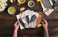 Мужская рука держа доску кухни с свежими сырыми рыбами Стоковая Фотография