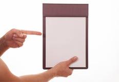 Мужская рука держа доску сзажимом для бумаги с пустыми листом бумаги и indi Стоковая Фотография