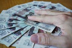 Мужская рука держа свои пальцы на круге созданном рублей русской валюты русских на деревянном столе Стоковые Изображения RF
