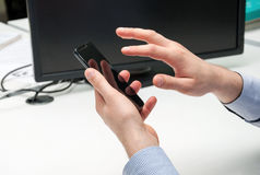 Мужская рука держа smartphone и касаясь своему экрану датчика Стоковое фото RF