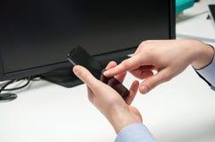 Мужская рука держа smartphone и касаясь своему экрану датчика Стоковое Изображение