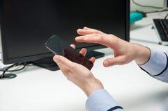 Мужская рука держа smartphone и касаясь своему экрану датчика Стоковые Фотографии RF