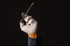 Мужская рука держит ноготь гроба как сигарета Стоковая Фотография