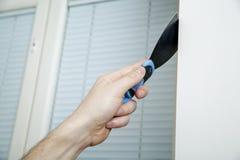 Мужская рука держит нож замазки на стене около угла Стоковые Фотографии RF