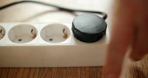 Мужская рука затыкая штепсельную вилку власти черных в белое множественное гнездо внутри помещения в замедленном движении Концепц акции видеоматериалы