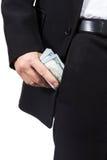 Мужская рука кладет деньги в его карманн брюк Стоковые Изображения RF