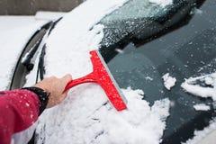 Мужская рука очищая автомобиль от снега с красным скруббером Стоковое фото RF