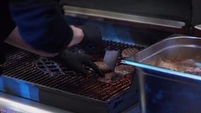 Мужская рука плитаа принимает вне пирожки бургера со шпателем от опаленного лотка гриля акции видеоматериалы