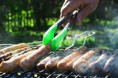 Мужская рука повернула сосиски над открытым барбекю огня конец вверх напольно Стоковое Изображение