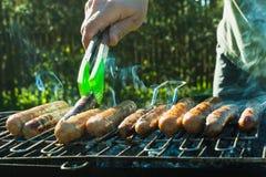 Мужская рука повернула сосиски над открытым барбекю огня конец вверх напольно Стоковые Изображения RF