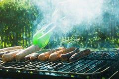 Мужская рука повернула сосиски над открытым барбекю огня конец вверх напольно Стоковое фото RF