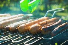 Мужская рука повернула сосиски над открытым барбекю огня конец вверх напольно Стоковая Фотография RF