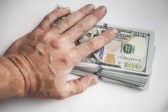 Мужская рука покрывает пачку долларов США Стоковые Изображения RF