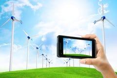 Мужская рука принимает фото телефоном с ветротурбиной для индустрии e Стоковое Изображение RF