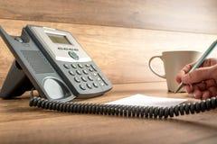 Мужская рука принимая важные примечания по мере того как он отвечает звонку на calss Стоковые Изображения