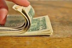 Мужская рука проверяя и подсчитывая кучу американской валюты США денег, USD на деревянной предпосылке как символ богатства Стоковое фото RF