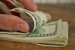 Мужская рука проверяя и подсчитывая кучу американской валюты США денег, USD на деревянной предпосылке как символ богатства Стоковые Фото