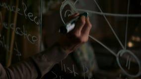 Мужская рука с белым сочинительством отметки на стеклянных номерах доски и схеме, концепции дела шток Рука молодого человека сток-видео