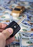 Мужская рука с ключом автомобиля на предпосылке долларовых банкнот Стоковое Фото