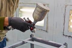 Мужская рука с оружием краски для пульверизатора, крася деталями автомобиля Стоковое Фото