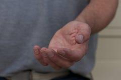 Мужская рука умоляя помощи Стоковые Фотографии RF