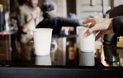 Мужская рука хватает кофе взятия отсутствующий от счетчика в кофейне Стоковые Изображения RF