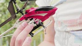 Мужская рука ` s держит красный nano вертолет игрушки и кладет обручальное кольцо на свои скиды акции видеоматериалы