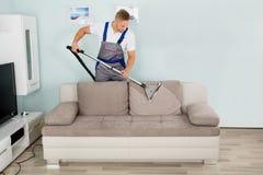 Мужская софа чистки работника с пылесосом Стоковая Фотография