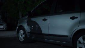 Мужская тень бандита идя на автостоянку ночи, систему анти--угона, городское злодеяние сток-видео