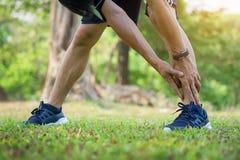 Мужская тренировка бегуна в холодной зиме делая протягивать ноги подогрева Стоковые Фото