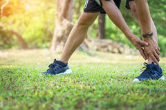 Мужская тренировка бегуна в холодной зиме делая протягивать ноги подогрева Стоковое фото RF