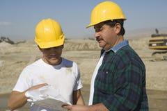 Мужские архитекторы обсуждая на строительной площадке Стоковое фото RF