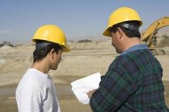 Мужские архитекторы обсуждая на строительной площадке Стоковые Фото