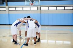 Мужские баскетболисты средней школы в груде имея беседу команды на суде стоковые изображения rf