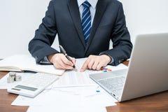 Мужские бизнесмены которые определяют данные в виде таблиц стоковое фото