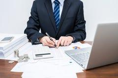 Мужские бизнесмены которые определяют данные в виде таблиц стоковая фотография