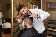 Мужские волосы вырезывания парикмахера усмехаясь клиента человека Стоковая Фотография RF