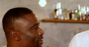 Мужские друзья говоря друг с другом в баре на ресторане 4K 4k акции видеоматериалы