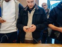 Мужские друзья сравнивая покупающ самое последнее iphone x Стоковые Фото