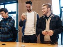Мужские друзья сравнивая покупающ самое последнее iphone x Стоковое фото RF